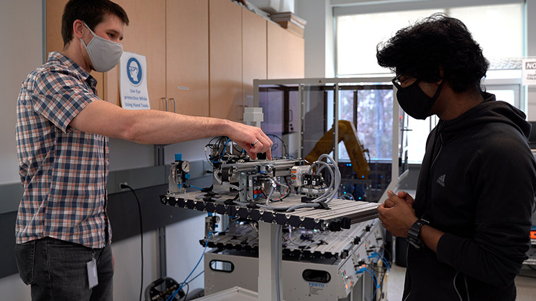 Assistant Professor of Teaching Dean Richert and student Ram Dershan prepare a workstation that will be used for the industrial automation micro-credential course.