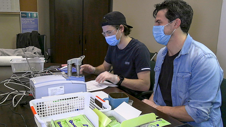 Third-year UBCO nursing student Thomas Pool works alongside community volunteer and registered nurse Sean Garden, as they check drug samples at Living Positive Resource Centre in downtown Kelowna.