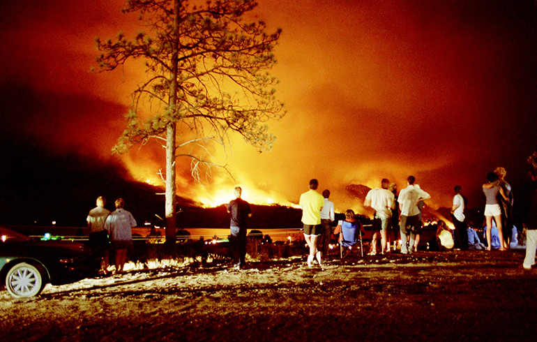 A group of residents watching the 2003 Okanagan Mountain Park fire rages out of control