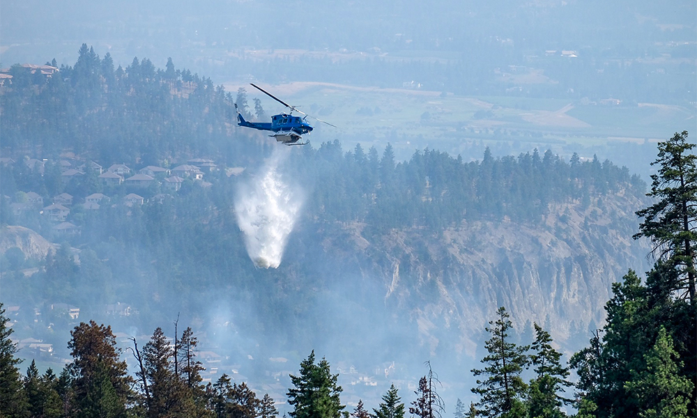 A helicopter dumping water on a forest wildfire